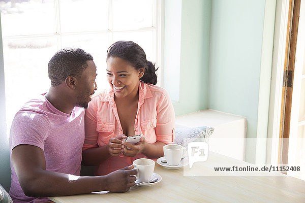 Smiling couple using cell phone at breakfast