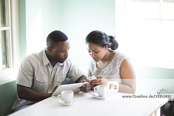 Smiling couple using cell phone and digital tablet at breakfast
