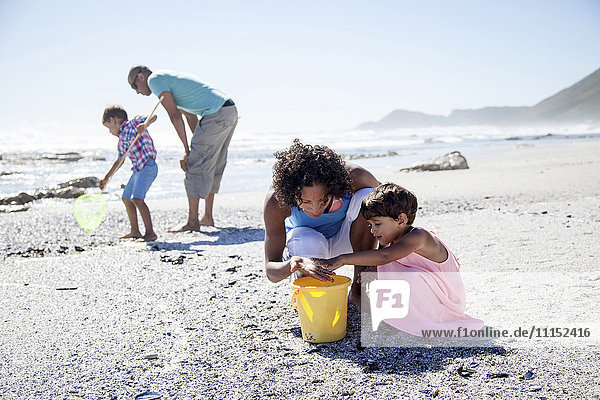 Mixed race family playing on beach