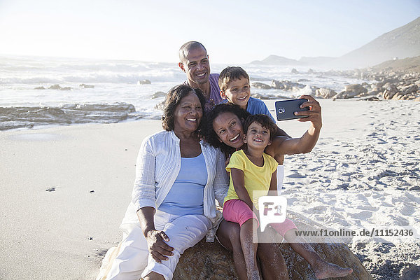 Mixed race multi-generation family taking cell phone selfie on beach