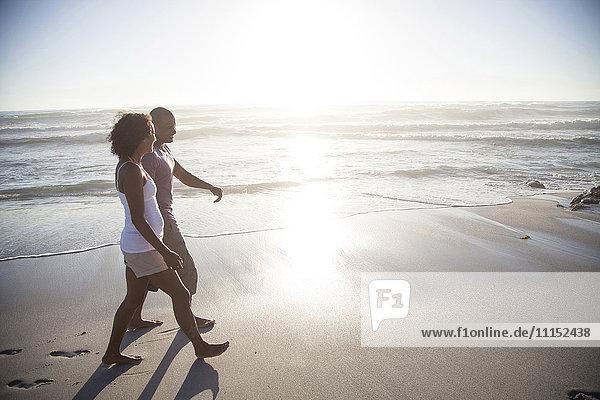 Mixed race couple walking on beach