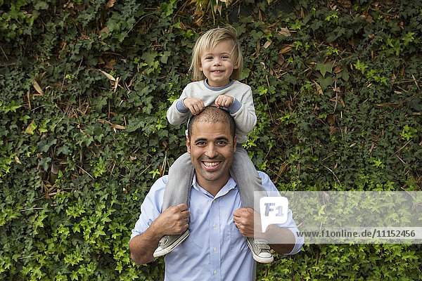 Hispanic father carrying son on shoulders near ivy wall