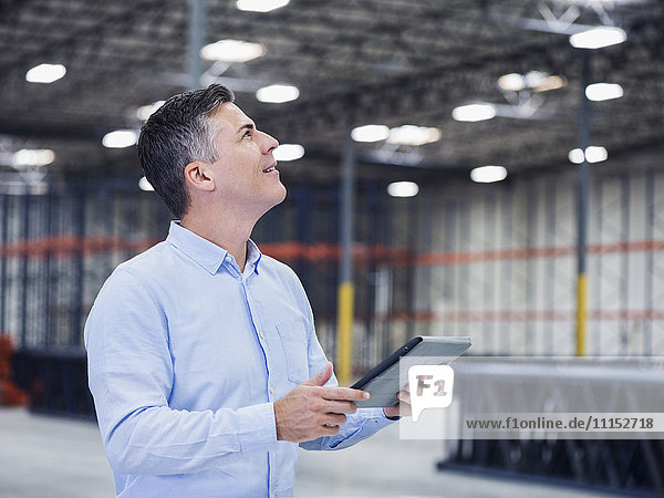 Caucasian businessman using digital tablet in empty warehouse