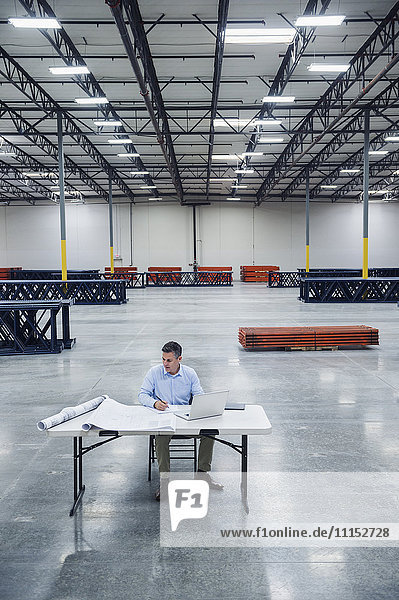 Caucasian architect reading blueprints in warehouse