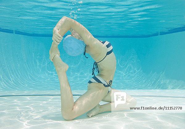Underwater view of Caucasian woman practicing yoga in swimming pool