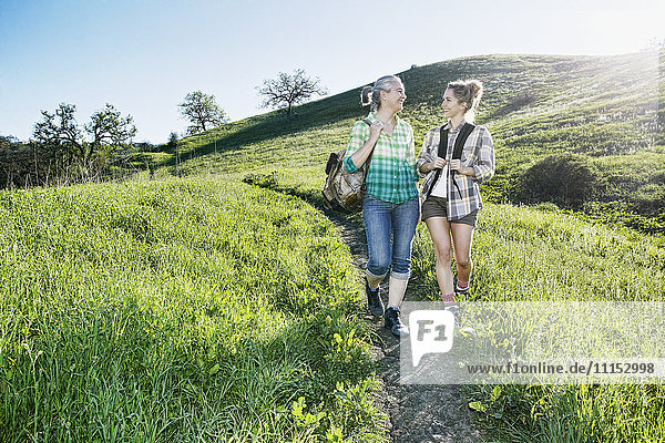 Caucasian mother and daughter walking on grassy hillside