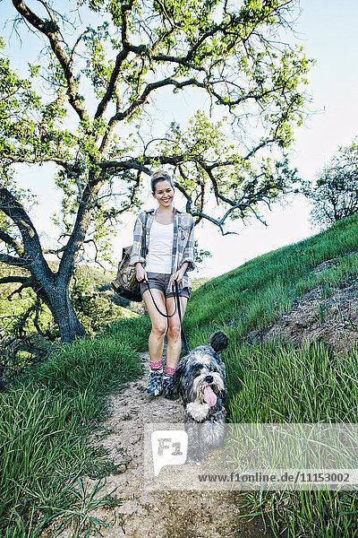 Caucasian woman walking dog on grassy hillside Caucasian woman walking dog on grassy hillside