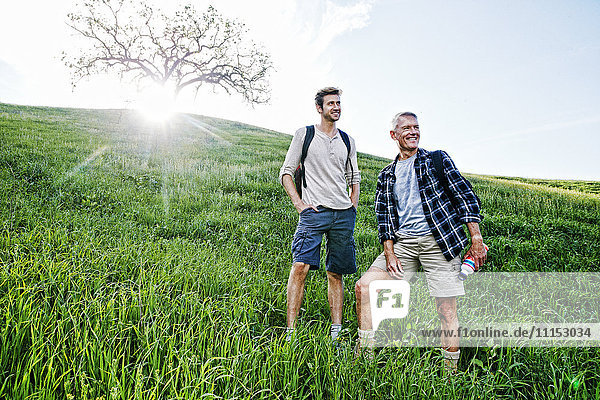 Caucasian father and son standing on grassy hillside Caucasian father and son standing on grassy hillside