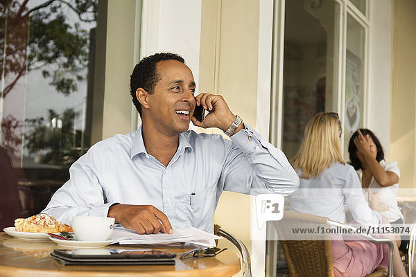 Businessman talking on cell phone in cafe