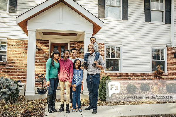 Black family smiling outside house