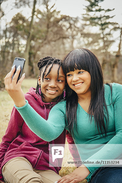 Black sisters taking selfie outdoors