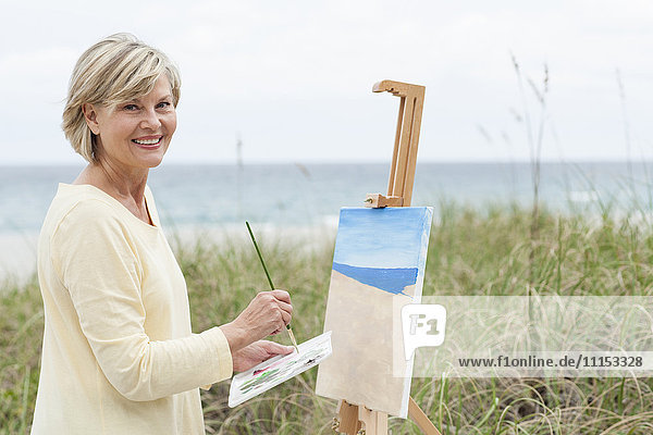 Older Caucasian woman painting beach outdoors