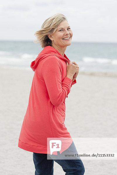 Older Caucasian woman walking on beach