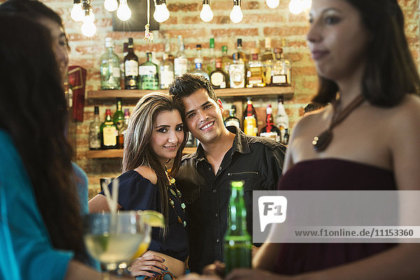 Hispanic couple smiling in bar