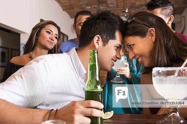Hispanic couple touching foreheads in bar