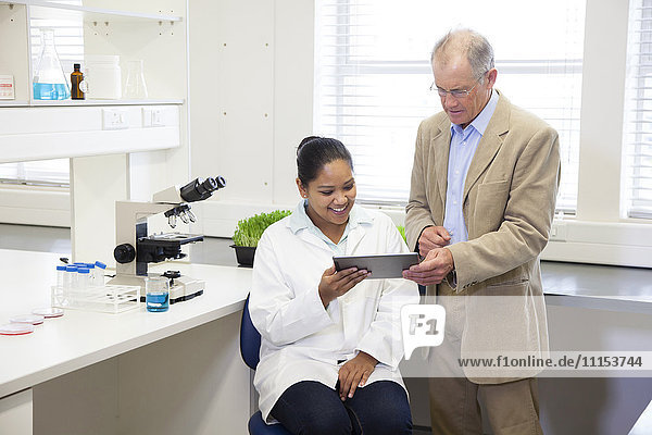 Businessman and scientists using digital tablet in laboratory