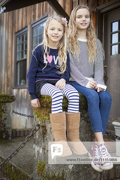Sisters sitting on mossy pedestal