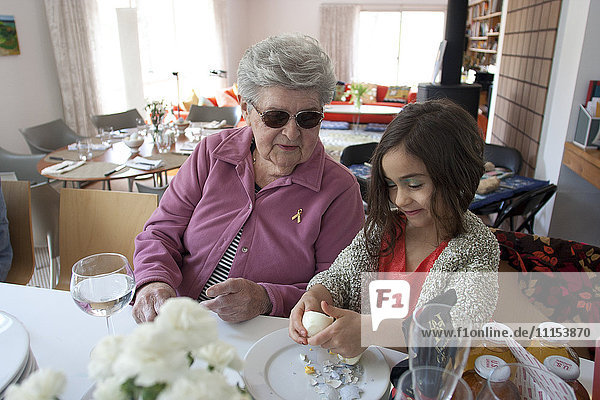 Grandmother and granddaughter cooking at table