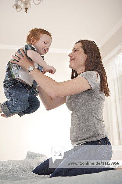 Mother and son playing on bed