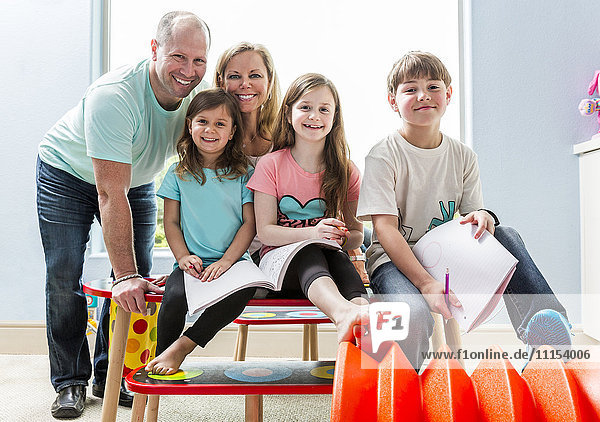 Caucasian family smiling at table in playroom
