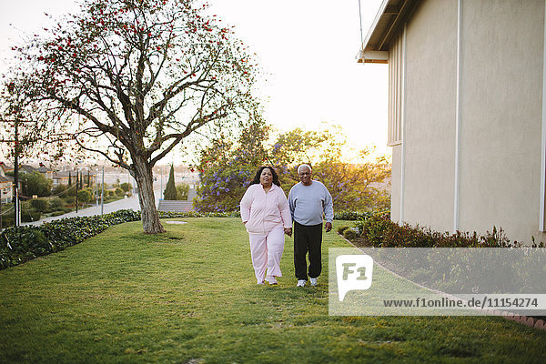 Couple walking in backyard of apartment building