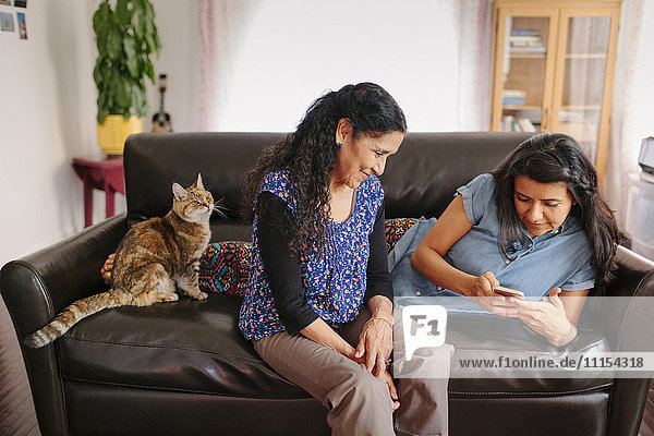 Hispanic mother and daughter using cell phone on sofa
