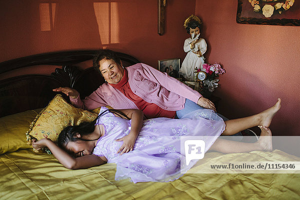 Hispanic grandmother and granddaughter laying on bed