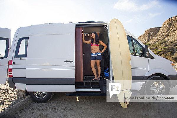 Hispanic surfer standing in van with surfboard