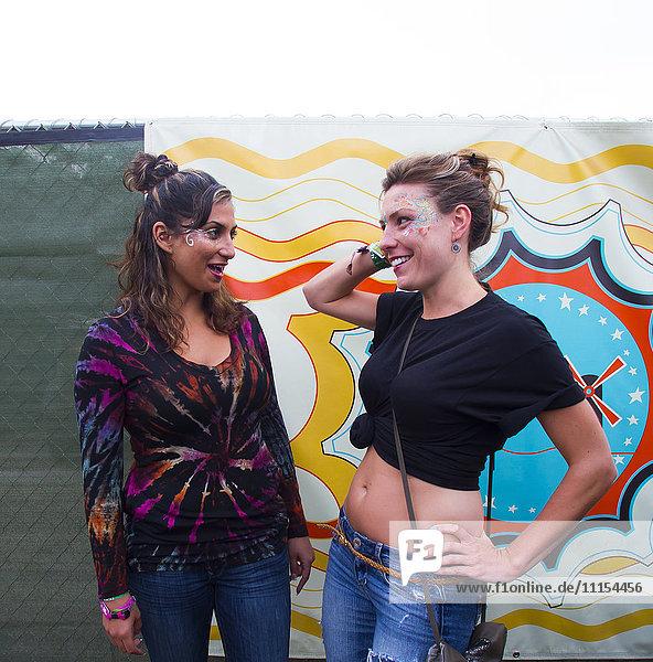 Women talking near multicolor mural