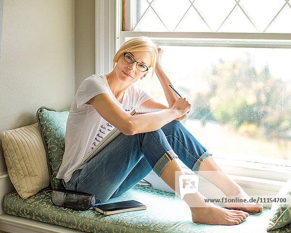 Caucasian woman sitting in windowsill
