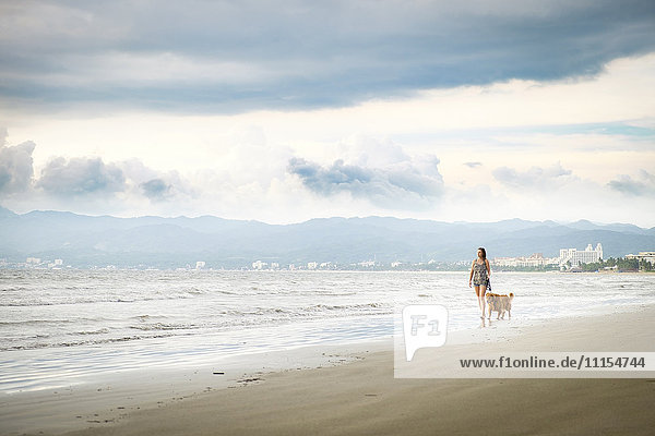 Mexico  Nayarit  Young woman walking Golden Retriever dog at the beach