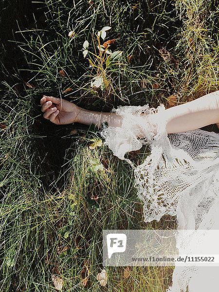 Bride wearing wedding dress in tall grass