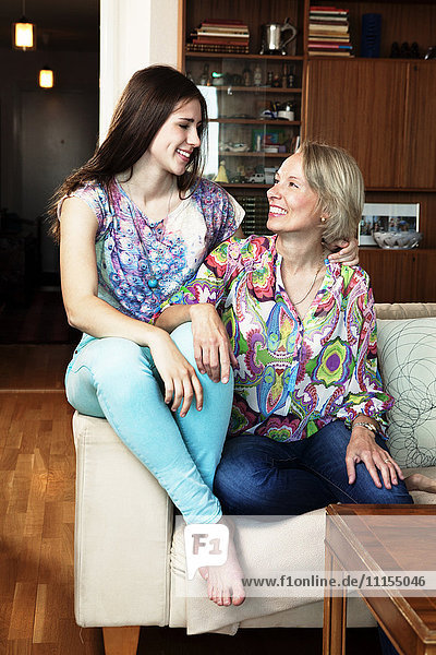 Caucasian mother and daughter sitting on sofa