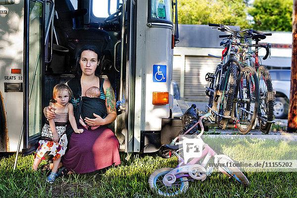 Mother and children sitting in bus doorway
