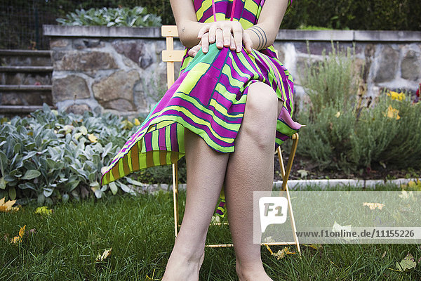Woman sitting with legs crossed in chair in backyard