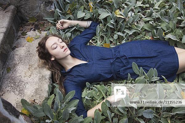 Woman sleeping in leafy garden