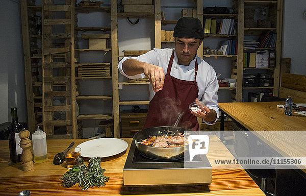 Mann gießt Salz auf Rinderbäckchen in einer Pfanne mit sautiertem Gemüse