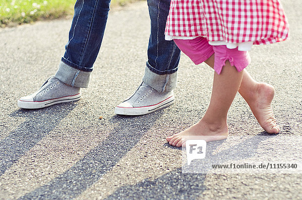 Children barefoot and with sneakers standing on concrete