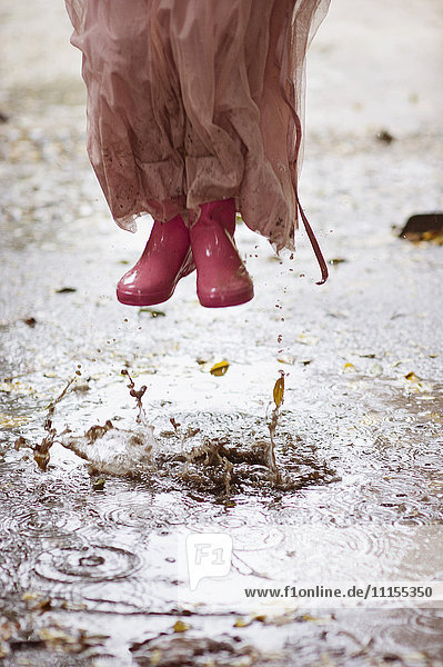 Caucasian girl in rain boots jumping in rain puddles