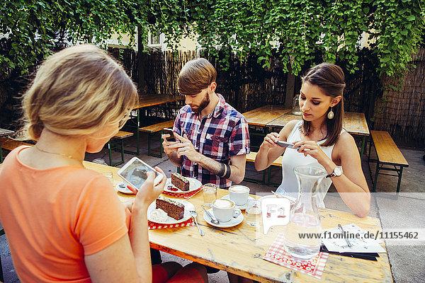 Freunde im Freien mit Kaffee und Kuchen beim Fotografieren mit dem Handy