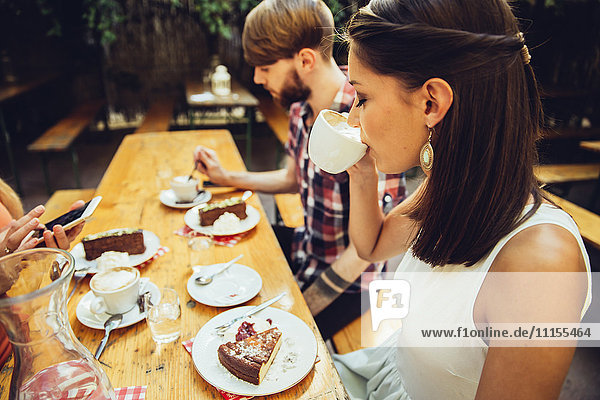 Friends sitting outdoors having coffee and cake