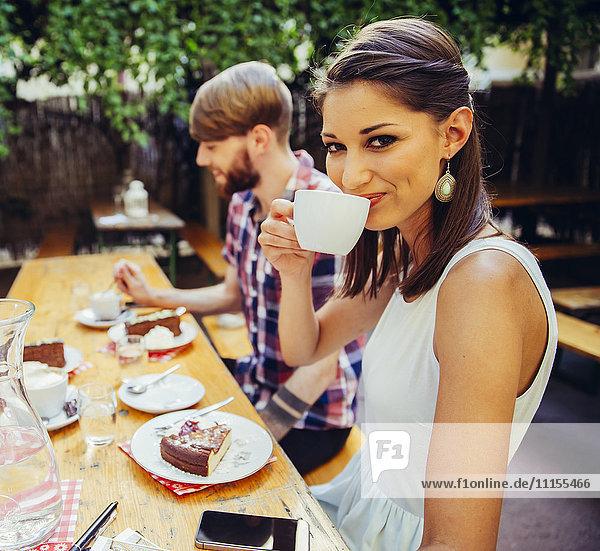 Lächelnde junge Frau mit Freund im Freien bei Kaffee und Kuchen