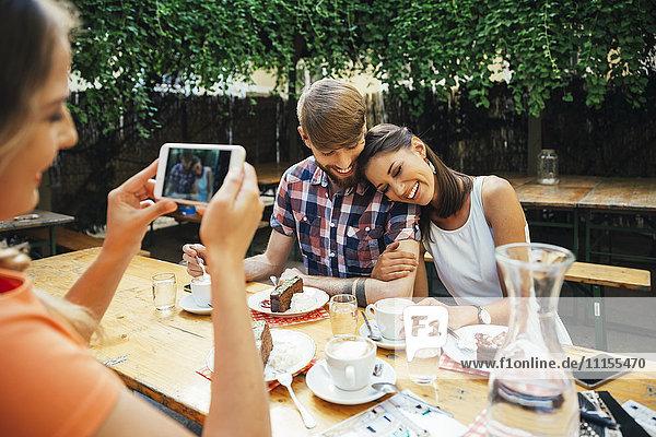 Frau macht Handyfoto von einem Paar im Freien mit Kaffee und Kuchen