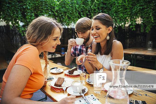 Freunde mit Handy im Freien bei Kaffee und Kuchen