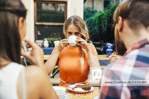 Freunde im Freien bei Kaffee und Kuchen