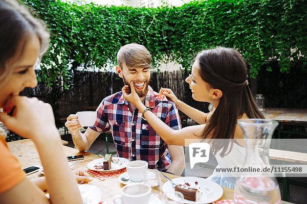 Glückliches junges Paar mit Freund im Freien bei Kaffee und Kuchen