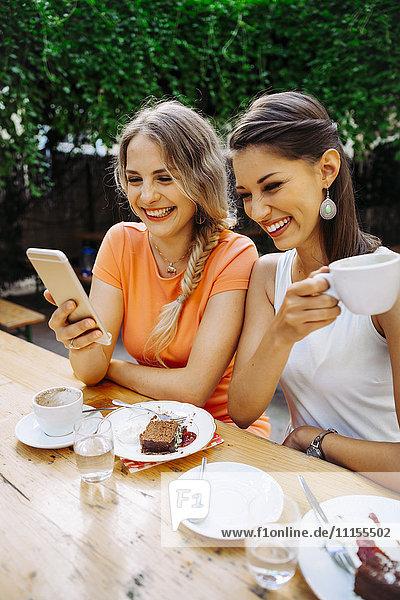Zwei junge Frauen mit Handybild im Outdoor-Café