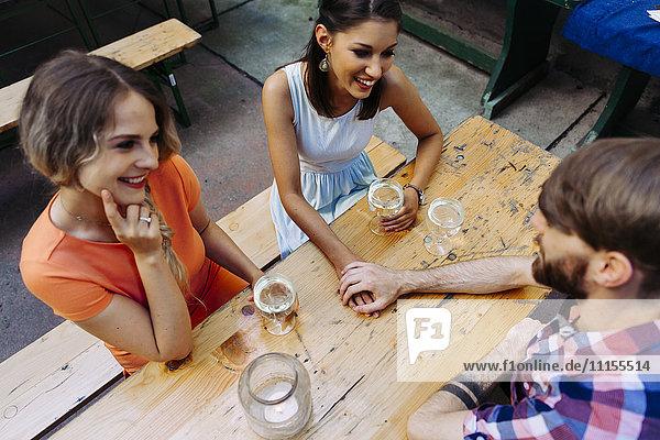Junges Paar und Freund trinkt Schorle im Pub