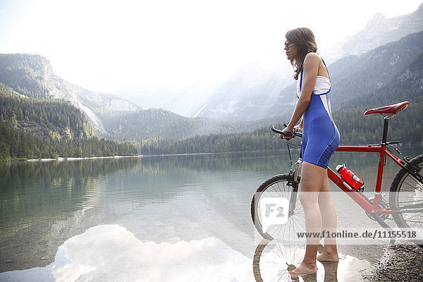 Caucasian woman with bicycle in remote lake