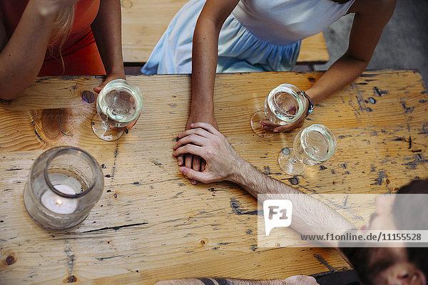 Junges Paar Hand in Hand und Freund trinkt Schorle in der Außenkneipe, Junges Paar Hand in Hand und Freund trinkt Schorle in der Außenkneipe
